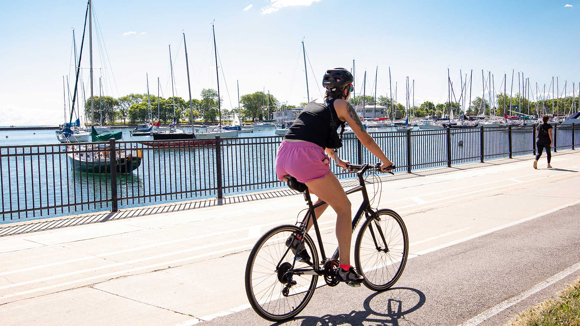 A woman rides her bike along the Lakefront Trail near Lake Michigan. Several boats are seen floating in the harbor behind her.